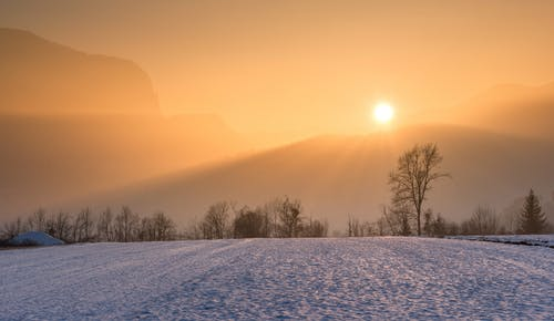 Landscape covered with snow and sunrise peaking behind a tree line and mountain peaks. How to find balance when overwhelmed with priorities.